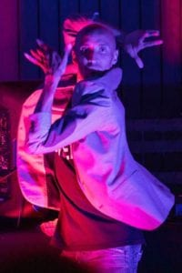 A Black dancer strikes a classic old school Vogue pose on a runway. His hands are around his face and he wears a light suit jacket, jeans and T Shirt. He is lit dramatically by pink and purple lighting.