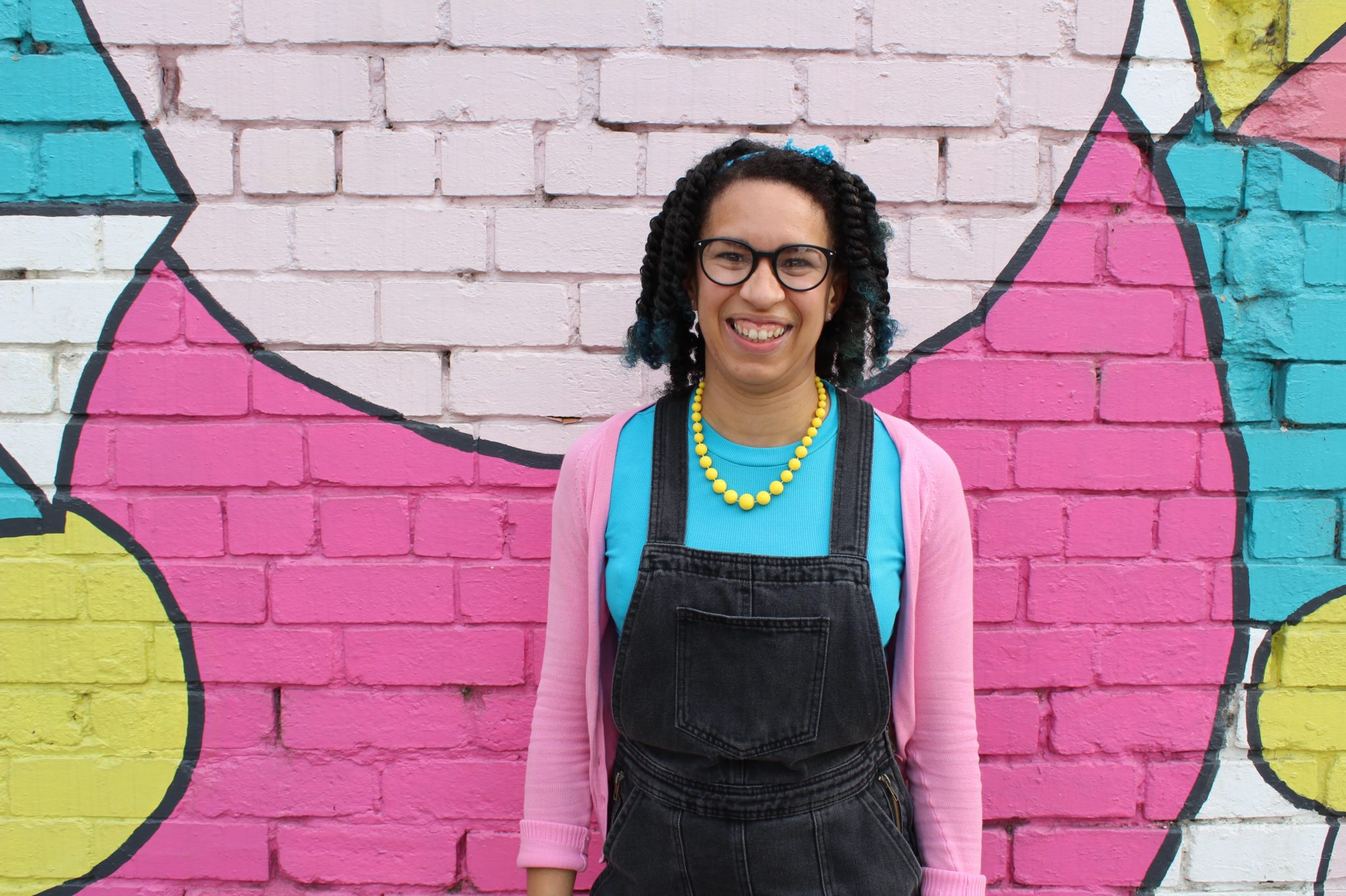 A Black woman with mid length hair stands in front a painted pink brick wall. She is wearing a turquoise tee with black dungarees and pink cardigan accessorised with bright yellow beaded necklace. She has on glasses and is smiling with an open smile at the camera