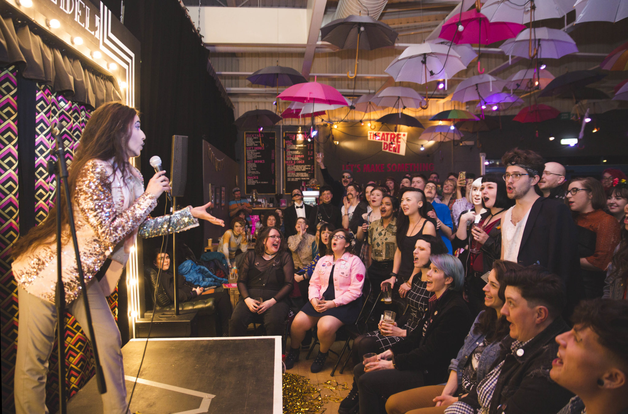 A slim, olive skinned drag king with long dark hair, stands on a small cabaret stage. In front of him is a crowd all whooping for him. They are lit by warm light and surrounded by lots of umbrellas hanging from the ceiling